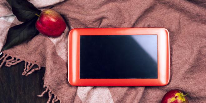 An IPad on a scarf with apples surrounding it.